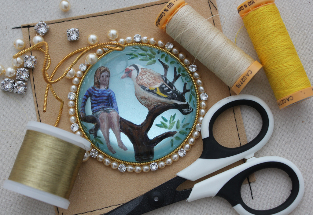 Stitching goldwork embroidery around the glass gems
