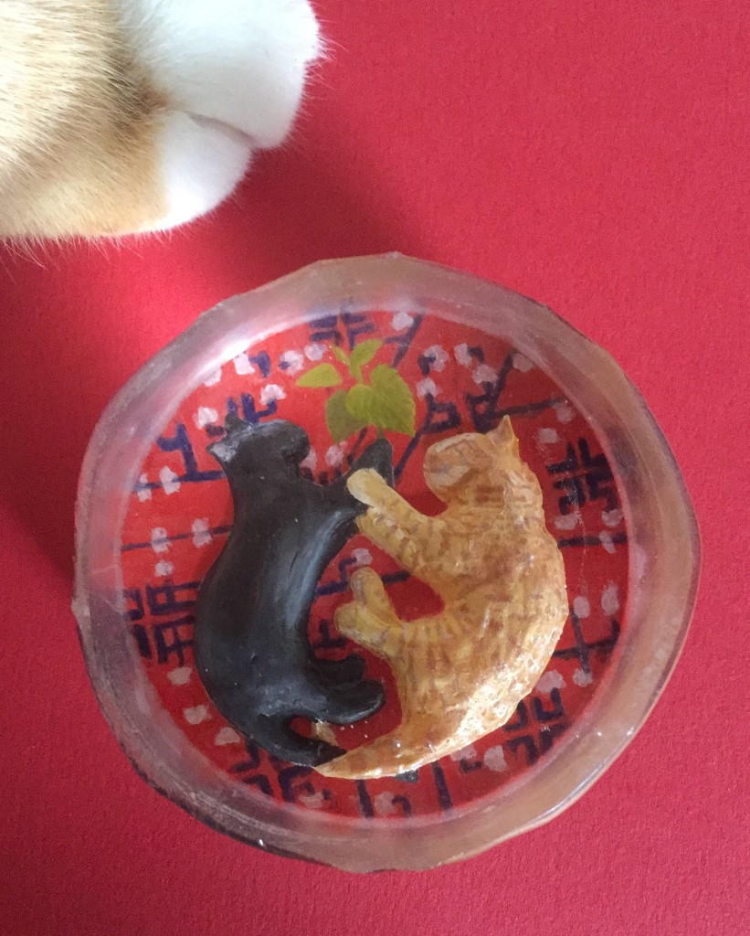 picture of a glass crystal with two cats on a carpet - one ginger, one black, holding a sprig of catmint