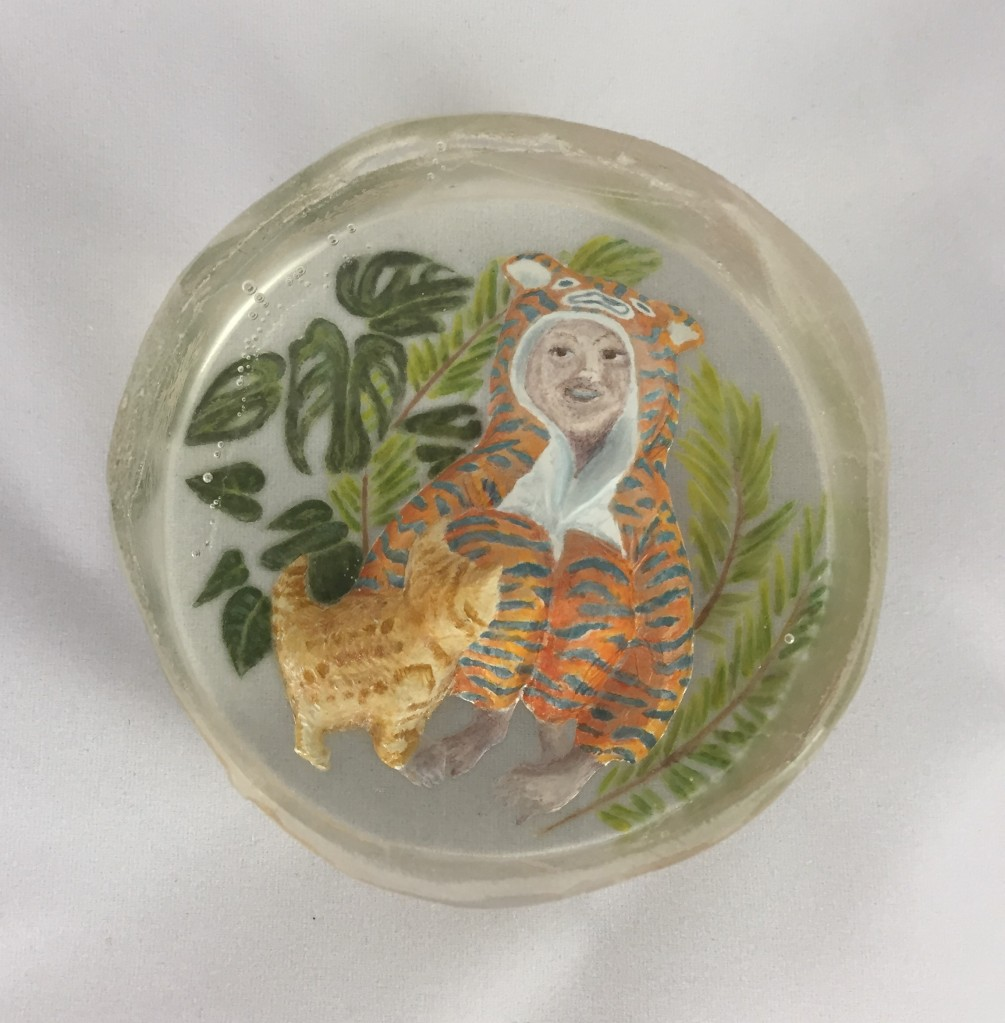 picture of glass crystal with a boy in a tiger onsie and a kitten