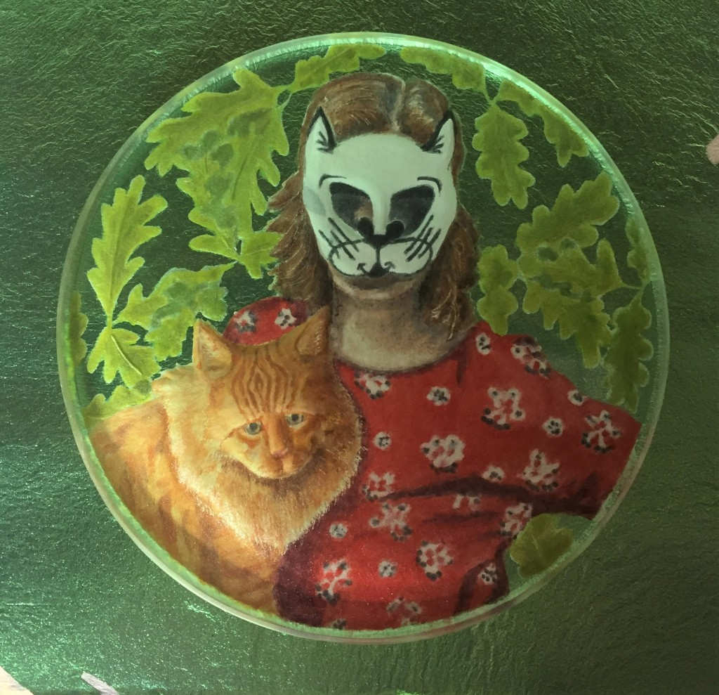 Picture of woman in a cat mask and a ginger cat