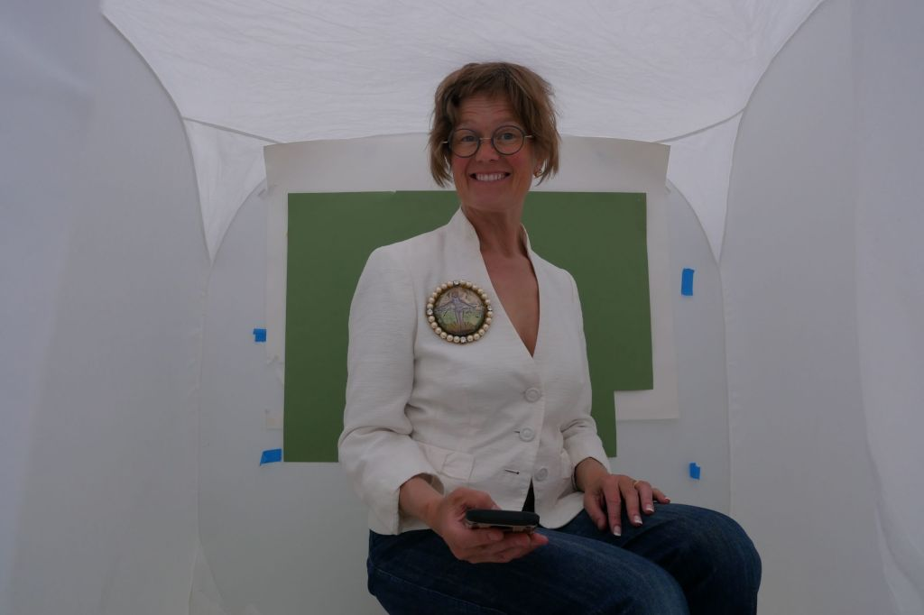 Picture of a woman sat in a small white photo tent wearing jeans and a cream top and wearing a large cast glass, engraved and enamelled essex crystal brooch