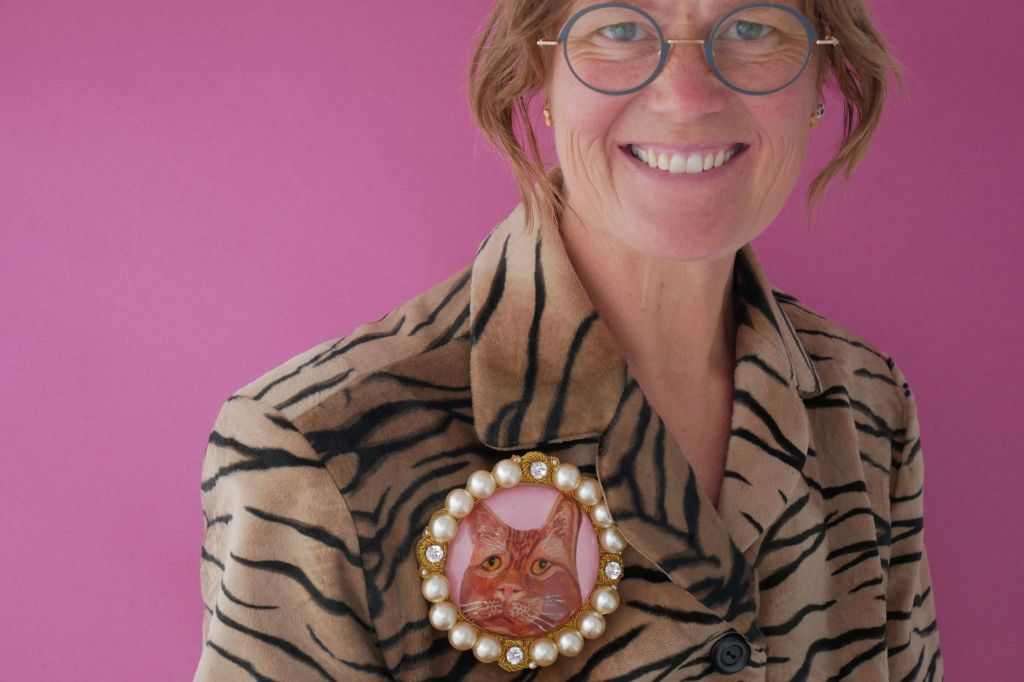 Picture of cast, engrved and enamelled borrch of a cat pinned to a fauz tiger skin coat worn by a woman